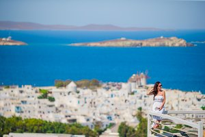 BYoung lady relaxing on the edge of swimming pool with beautiful view of amazing greek village