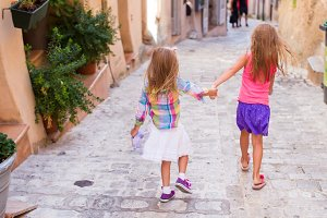 Adorable happy little girls outdoors in narrow street at small city