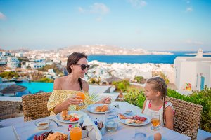 Family having breakfast at outdoor cafe with amazing view. Adorable girl and mother eating croissant on luxury hotel terrace