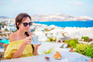 Beautiful girl having breakfast at outdoor cafe with amazing view on Mykonos town. Woman drinking hot coffee on luxury hotel terrace with sea view at resort restaurant.