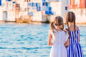 Little kids at Little Venice the most popular tourist area on Mykonos island, Greece. Back view of beautiful girls look at Little Venice background.