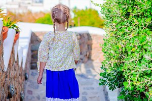 Adorable girl at street of typical greek traditional village on Mykonos Island, in Greece