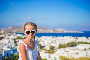 Portrait little girl in Mykonos town background amazing view of traditional white houses