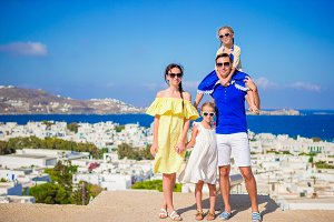 Family vacation in Europe. Parents and kids looking at camera background Mykonos island in Greece