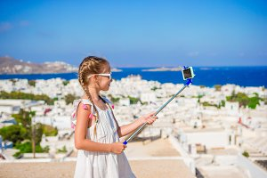 Little girl taking selfie background Mykonos town in Greece