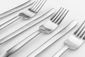 Modern silverware or flatware set isolated on white. Different shapes merged together. Image taken from above, top view