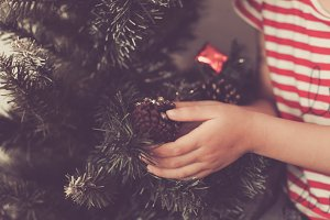 Cute baby girl decorate and play around the chirstmas tree