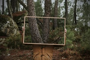young holding frame with nature, concept of environment