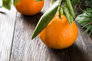 Fresh tangerines with leaves and ripe mandarins on wooden table