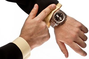 Man's hand in the suit pointing on his watch