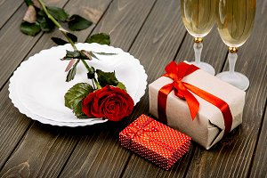 Plate with red rose and gift boxes