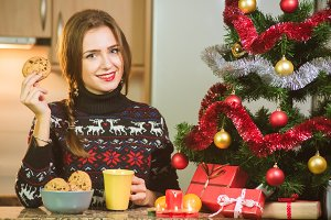 Young happy woman holding chocolate cookies close to the Christmas tree