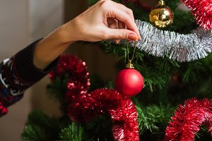 Decorating Christmas tree on bright background with presents