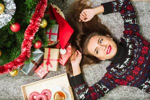 Young cute happy girl in sweater with deer lying on the floor at home. New Year and Christmas celebration