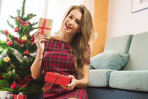 Attractive happy woman sitting near decorated Christmas tree and enjoying her presents