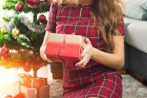 Attractive happy surprised woman sitting near decorated Christmas tree and enjoying her presents