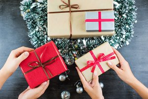 Christmas gifts on a table with black background and hands holding presents