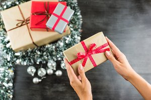 Christmas gifts on a table with black background and hands holding present