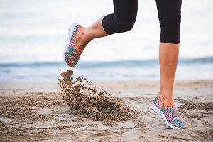 Closeup of female legs running on beach at sunrise in morning with sand in-motion