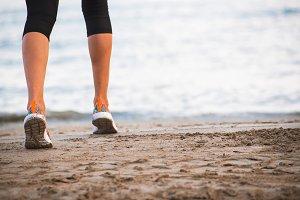 Closeup of female legs running on beach at sunrise in morning