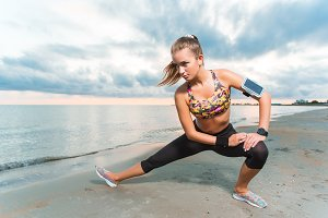 Young fit girl stretching on beach at sunrise