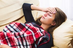 Sick woman lying on sofa under wool blanket