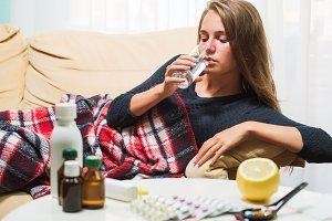 Sick woman lying on sofa under wool blanket drinking water