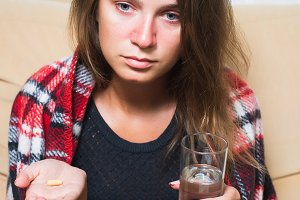 Sick woman holding pill and glass of water
