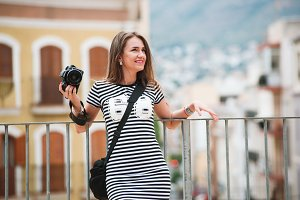 Portrait of young tourist with camera