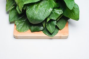 Closeup Fresh harvested spinach on a wooden table.