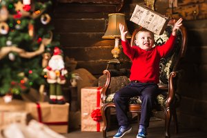 Small boy sitting in chair with present next to Christmas tree and gifts