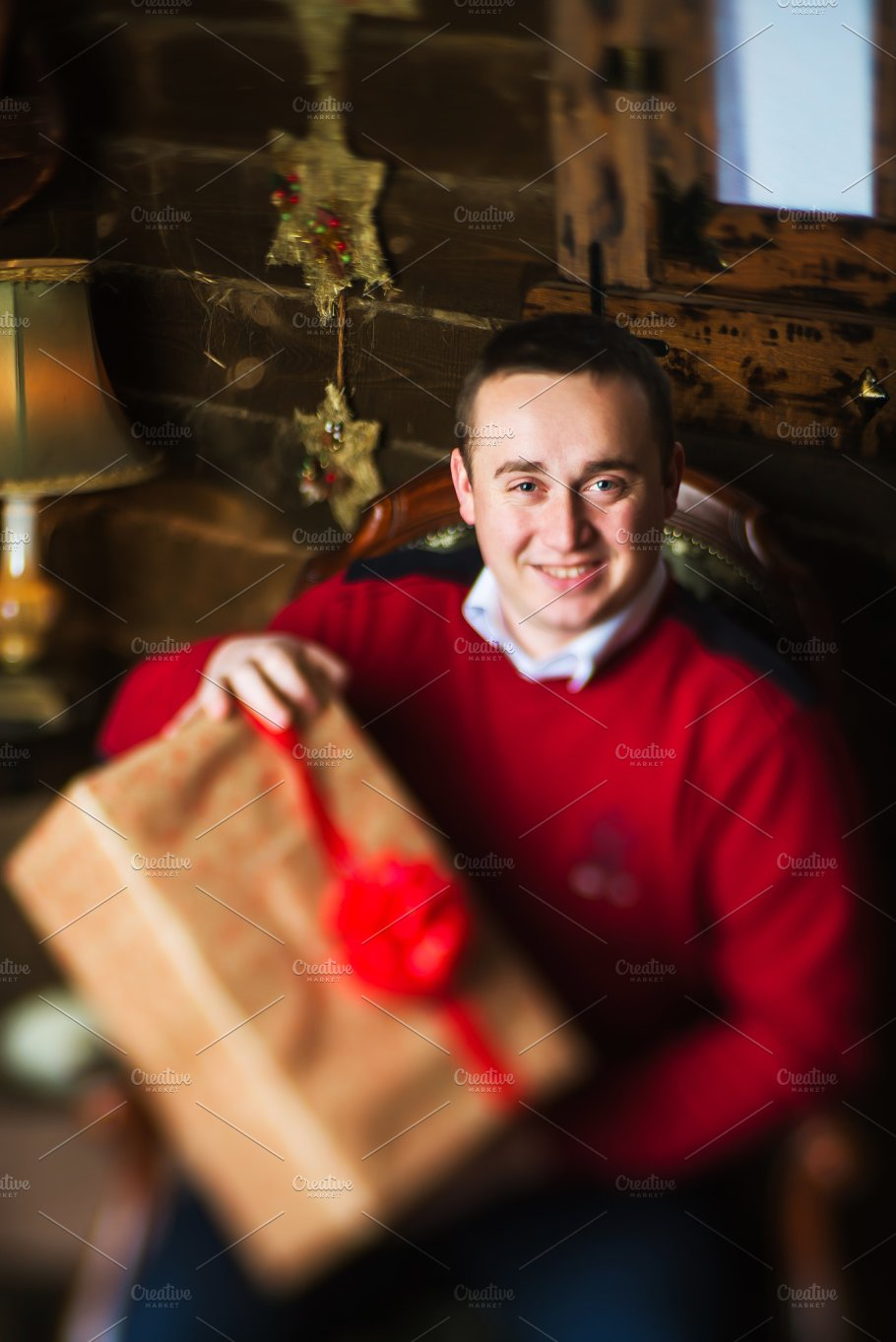 Young Man Holding Present Next To Christmas Tree And Gifts Holidays