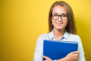 Cute business woman in spectacles holding a folder