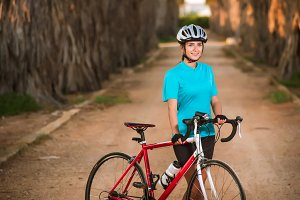 Portrait of young female cyclist standing with bike on palms off-road
