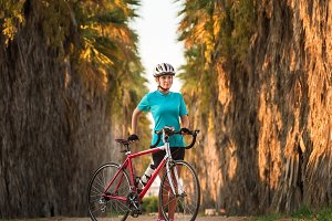 Young female cyclist standing with bike on palms road