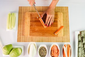 Close up picture of young lady's hands slicing crab sticks