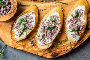Sandwiches with cream cheese and garlic edible flowers, olive board