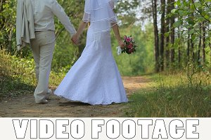 Bride and groom walk in the woods