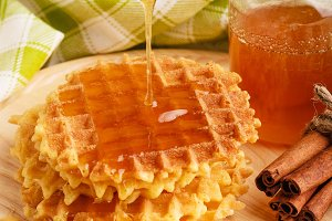 Waffles with honey on a wooden surface