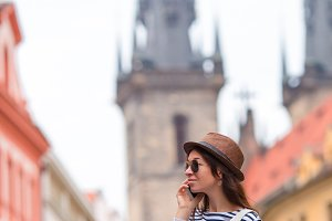 Young woman talking by smartphone background famous castle in european city. Caucasian tourist walking along the deserted streets of Prague, Europe.