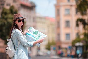 Happy young woman with a city map in city. Travel tourist woman with map in Prague outdoors during holidays in Europe.