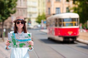 Young tourist girl with a city map searching attraction outdoors. Travel caucasian woman with map outside during holidays in Europe.