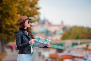 Happy young woman with a city map in city. Travel tourist woman with map outdoors during holidays in Europe.