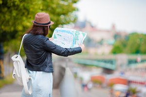 Beautiful woman with touristic citymap in the city. Happy girl enjoy european vacation holiday in Europe.