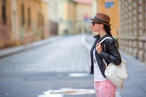 Young caucasian woman listen music in european city outdoors