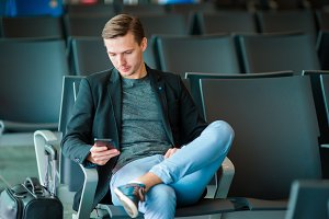 Urban business man talking on smart phone traveling inside in airport. Casual young businessman wearing suit jacket. Handsome male model. Young man with cellphone at the airport while waiting for boarding.