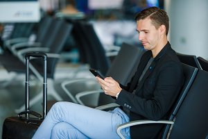 Young man with cellphone inside in airport. Young man with smartphone at the airport while waiting for boarding.