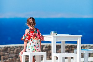 Adorable little girl having breakfast at outdoor cafe with sea view. Time for lunch.