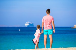 Happy dad and little girl enjoy summer vacation