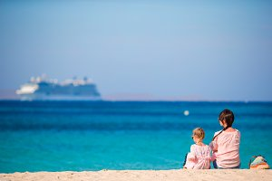 Young mom and adorable girl at beach on sunny day with view of big liner